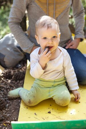 sitting on the ground: Little boy biting a cone while sitting on a touristic mat on the ground, mother behind the boy