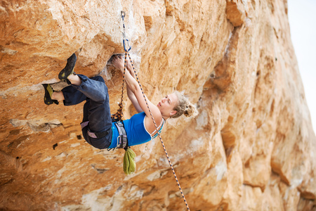 lead rope: Young female rock climber struggling to make next movement up Stock Photo