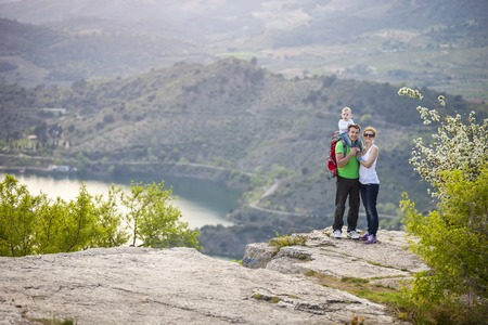 Young couple with toddler boy standing on cliff and smiling photo