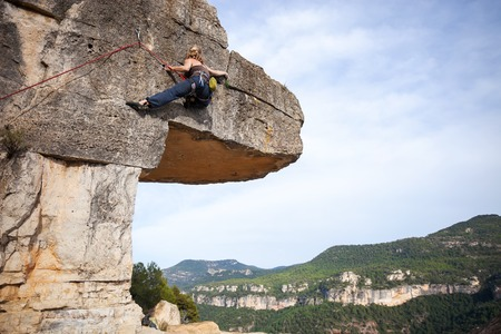 climbing wall: Woman climber on challenging route on cliff Stock Photo