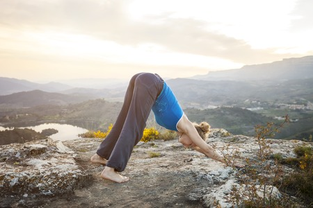 downward: Young Caucasian woman performing downward dog yoga pose outdoors Stock Photo