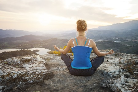 yoga rocks: Young woman sitting on a rock and enjoying valley view. Girl sits in asana position.