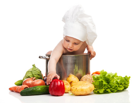 Little boy in chefs hat reaching for bell pepper while sitting in large casserole over white