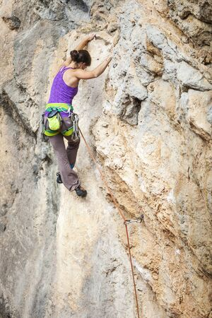 overhanging: Young female rock climber on overhanging cliff