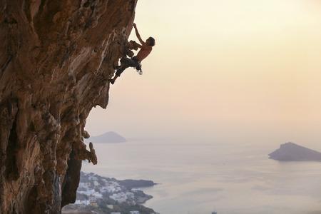 夕暮れ、カリムノス島、ギリシャ男性ロック ・ クライマー