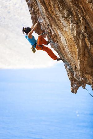 escalando: Escalador de roca femenino joven en un acantilado
