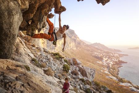 trepadoras: Joven mujer escalada plomo en la cueva con hermosa vista en segundo plano Foto de archivo