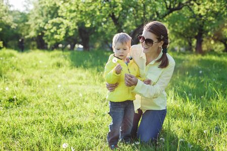 blowing dandelion: Toddler boy and his mom making with before blowing dandelion Stock Photo