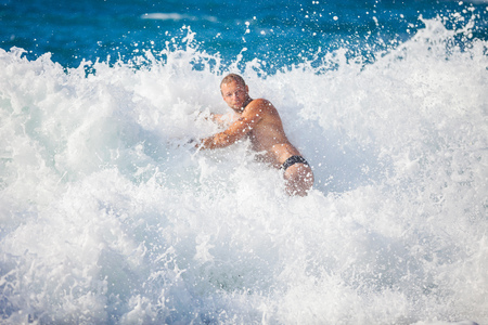 storming: Young man bathing in storming sea, high wave just washed his over, water in focus Stock Photo