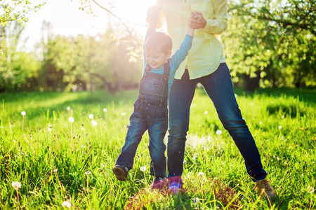 Toddler boy and his mom having fun in summer park, Image with backlight, some stay light in foreground Banque d'images