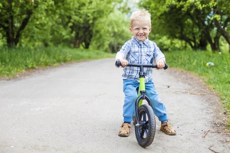 Happy little boy riding learner bike photo