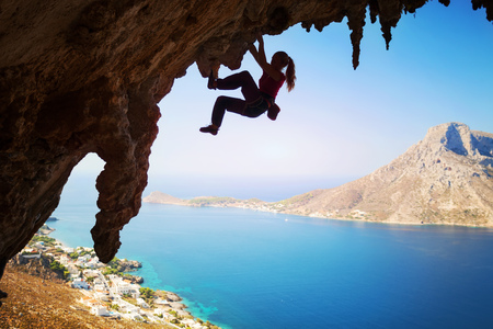 Silhouette of a young female rock climber on a cliff. Kalymnos Island, Greece