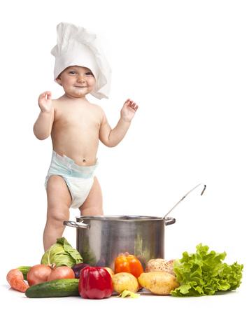 manos aplaudiendo: Niño pequeño alegre en el sombrero de cocinero jugando con la cazuela y hortalizas