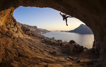 stijger: Mannelijke bergbeklimmer het beklimmen langs een dak in een grot bij zonsondergang Stockfoto