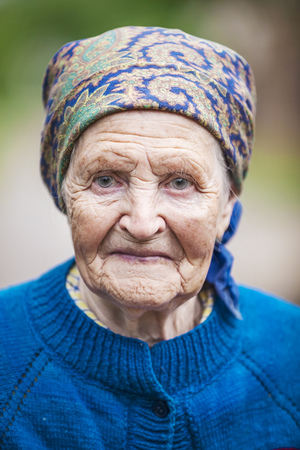 80s adult: Portrait of an aged woman smiling outdoors