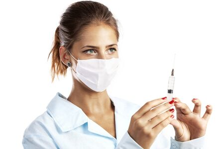 health professional: Doctor or nurse in face mask and lab coat holding syringe. Isolated over white.