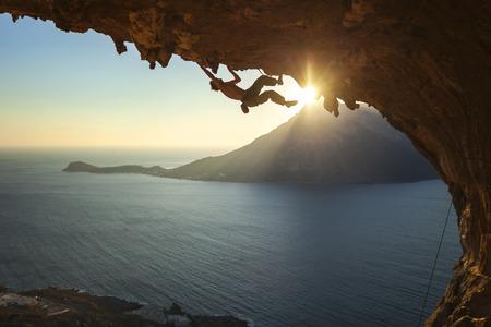 escalando: Hombre escalada escalador de roca a lo largo de un techo en una cueva en la puesta del sol