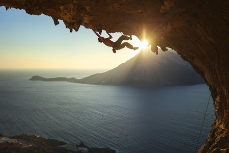 climber: Male rock climber climbing along a roof in a cave at sunset