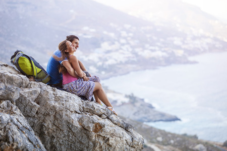 Young couple sitting on rock and enjoying beautiful view. Kalymnos Island, Greece. photo