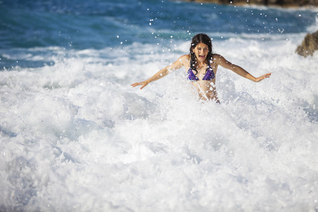 storming: Young woman bathing in storming sea, high wave just washed her over