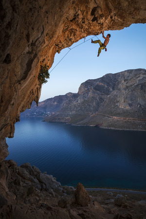 climb: Male rock climber on overhanging cliff, Kalymnos Island, Greece