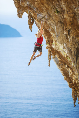 Female rock climber struggling on challenging route on cliff Banque d'images