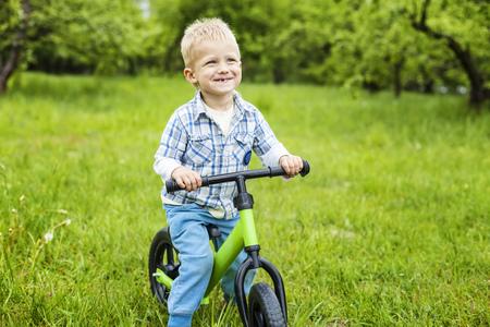 Happy little boy riding learner bike on grass photo