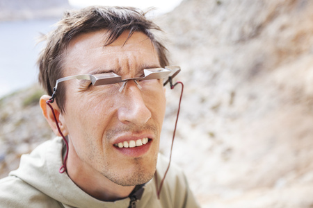 belay: Male climber wearing belay glasses while watching his partner climbing