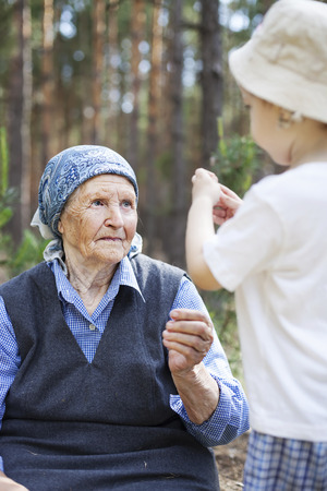 the great grandmother: Great grandmother and toddler boy talking during walk in park or forest