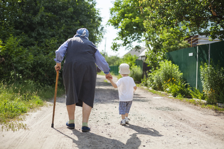 the great grandmother: Great grandmother and toddler boy holding hands while walking down street in countryside Stock Photo