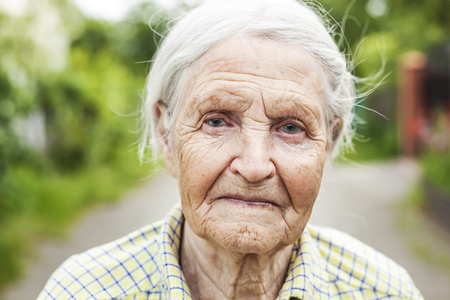 wrinkled: Portrait of an aged woman smiling outdoors