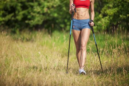 Ajuste a la mujer joven de senderismo con bastones de marcha nórdica en verano