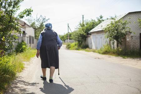 adult 80s: Senior woman walking down street in countryside