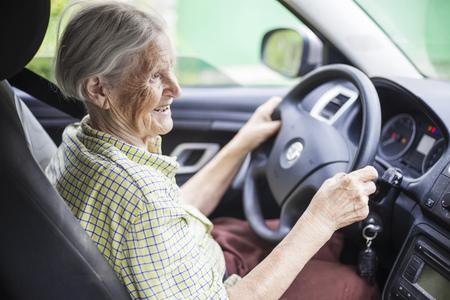 chofer: Mujer mayor alegre conducir un coche