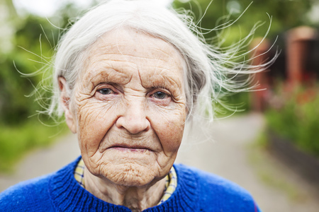 Portrait of an aged woman smiling outdoors