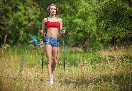 Fit young woman hiking with nordic walking poles in summertime Stock Photo