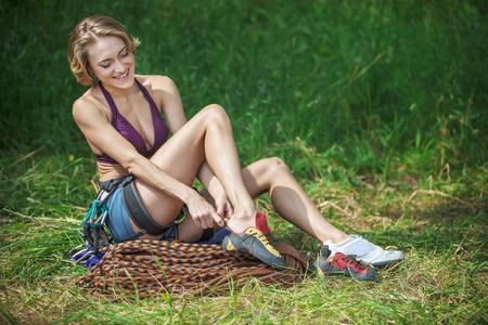 mujeres sentadas: escalador alegre que pone en los zapatos que suben mientras está sentado en la hierba