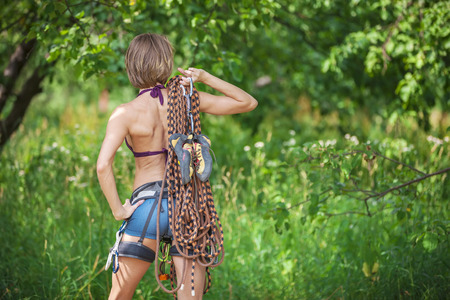 safety harness: Young female rock climber wearing safety harness and holding rope posing outdoors, rear view