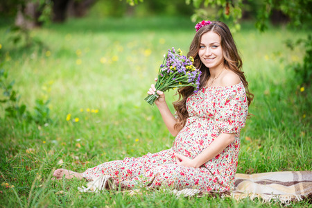 green park: Beautiful pregnant woman holding flowers outdoors in summer park Stock Photo