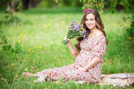embarazada: mujer que sostiene embarazadas hermosas flores al aire libre en el parque de verano