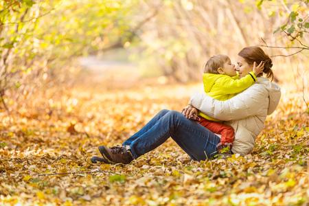 madre e figlio: Felice donna ed il suo piccolo figlio divertirsi in un parco di autunno. Il ragazzo baciare la madre nel naso