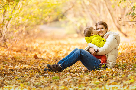 mom kiss son: Happy woman and her little son having fun in an autumn park. The boy kissing mother while sitting on her lap. Stock Photo