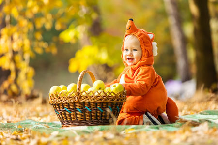 Cute baby boy dressed in fox costume sitting by basket with apples in autumn park