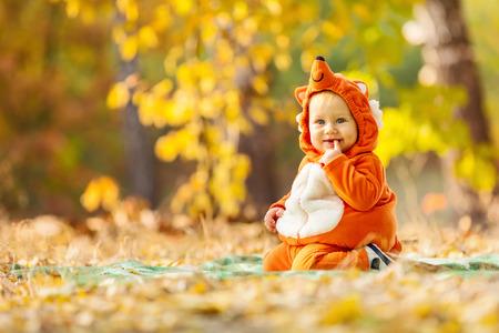 Cute baby boy dressed in fox costume in autumn park
