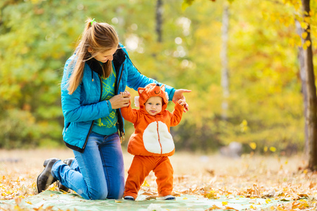 Young woman and her baby son in autumn park, boy dressed in fox costume photo
