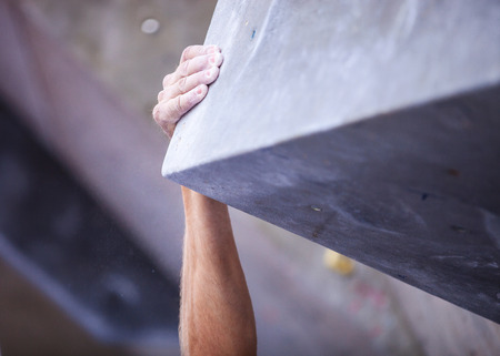 rock climbing: Closeup of mans hand on handhold on artificial climbing wall, hand in focus