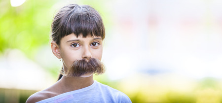 cover girls: Young girl with fake mustaches hiding her smile. Dental health concept.