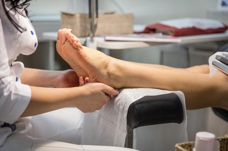 pedicura: Ver recortada de una mujer recibiendo un masaje de pies y pedicura