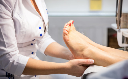 woman foot: Cropped view of woman getting foot massage Stock Photo