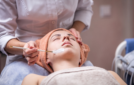 procedures: Young woman in spa salon, beautician applying facial mask to her, closeup view